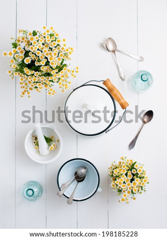 Chamomile flowers, white enamel cookware, glass bottles, vintage spoons on a white wooden background, cozy home rustic decor, vintage country living