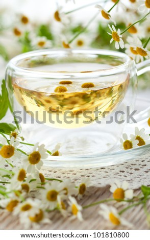 Chamomile tea in glass cup with flowers