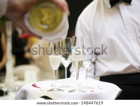 champagne being poured into a champagne flute by waitstaff