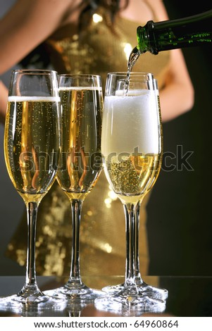 champagne being poured into elegant flutes with female in gold party dress in background