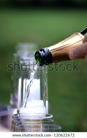 Champagne being poured into glass flute,with the glasses in the background.