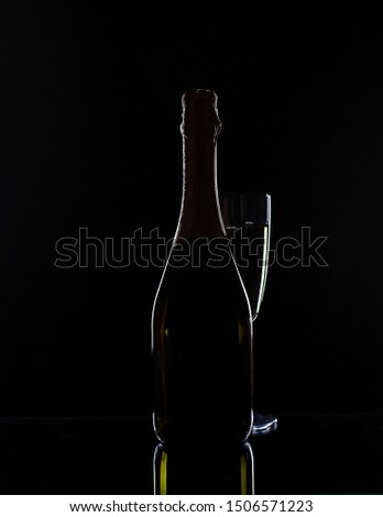 Champagne bottle and champagne glass in low key #1506571223