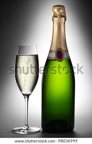 champagne bottle and glass in spotlight