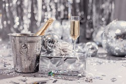 Champagne bottle in a bucket and a glass. Trending holiday decor foil shine. Stylish festive screensaver. Christmas new year party. Alcohol. Gift wrapped congratulation. Romance anniversary birthday