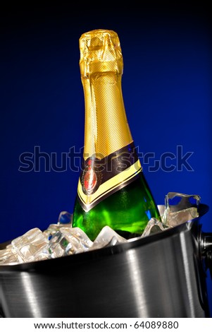 Champagne bottle in a bucket with ice on the dark