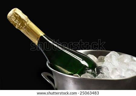 Champagne bottle in a cooler with ice on black background