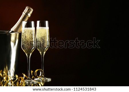 Champagne bottle in bucket with glasses on black background #1124531843