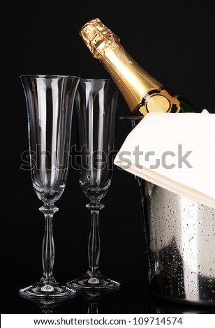 Champagne bottle in bucket with ice and glasses isolated on black