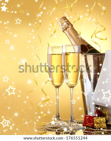 Champagne bottle in bucket with ice and glasses, on yellow background with lights #176551244