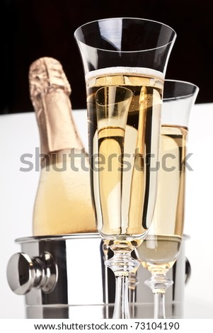 Champagne bottle in cooler and two champagne glasses.