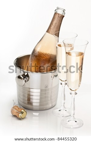 Champagne bottle in cooler and two champagne glasses. Isolated on a white.