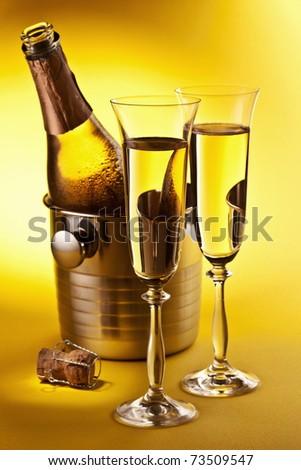 Champagne bottle in cooler and two champagne glasses. Isolated on a yellow.
