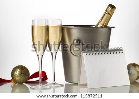 Champagne bottle in ice bucket with flutes and Christmas baubles