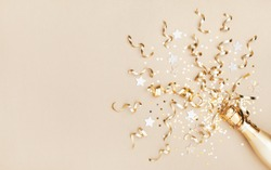 Champagne bottle with confetti stars and party streamers on gold festive background. Christmas, birthday or wedding concept. Flat lay.