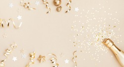 Champagne bottle with confetti stars, holiday decoration and party streamers on gold festive background. Christmas, birthday or wedding concept. Flat lay.