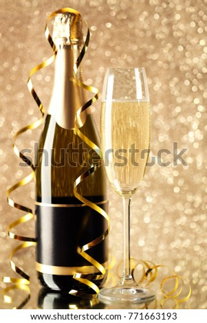 Champagne bottle with glass on lights background #771663193
