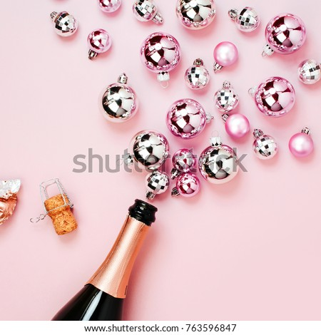Champagne bottle with pink and silver christmas balls. Flat lay, top view trendy holiday concept. #763596847