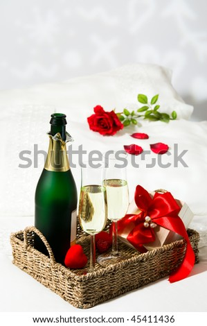 Champagne breakfast in bed with single red rose on pillow and gift wrapped in red ribbon