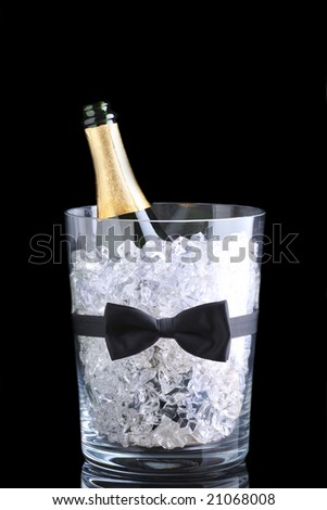 Champagne bucket with open bottle and bow tie over black