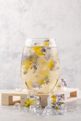 Champagne cocktail with ice and flowers on a light gray background. Light summer cool drink. Close-up.