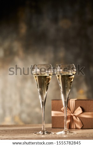 Champagne color image of gift box with bronze ribbon and two glasses of champagne. Golden colors. Copyspace for text.