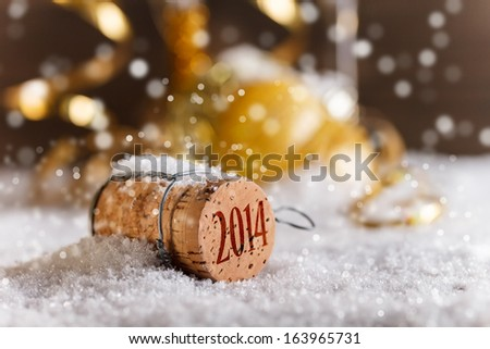 Champagne corks with 2014 year stamp in snow - stock photo
