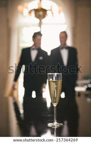 Champagne flute on a table with two men in the background