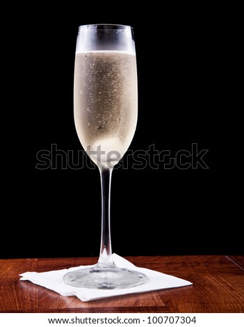 champagne flute served with sparkling wine and a sugar cube isolated on a black background
