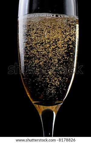 Champagne flute with bubbles against dark background
