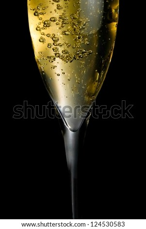 champagne flute with golden fine bubbles on black background
