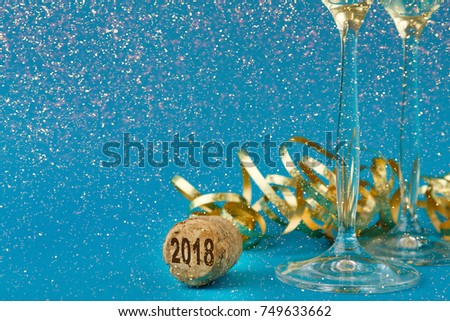 Champagne flutes and bottle cork with 2018 numbers at blue holiday background with golden glitters and tinsel. Celebrating christmas, new year or birthday. Mockup for xmas postcard, crop #749633662