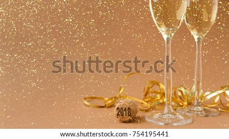 Champagne flutes and bottle cork with 2018 numbers at golden holiday background with glitters and tinsel. Celebrating christmas, new year or birthday. Mockup for xmas postcard, crop #754195441