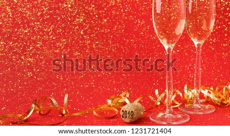 Champagne flutes and bottle cork with 2019 numbers at red holiday background with golden glitters and tinsel. Celebrating christmas, new year or birthday. Mockup for xmas postcard, crop #1231721404