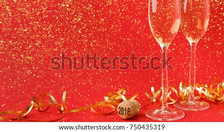 Champagne flutes and bottle cork with 2018 numbers at red holiday background with golden glitters and tinsel. Celebrating christmas, new year or birthday. Mockup for xmas postcard, crop #750435319