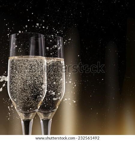 Champagne flutes on black background, celebration theme.