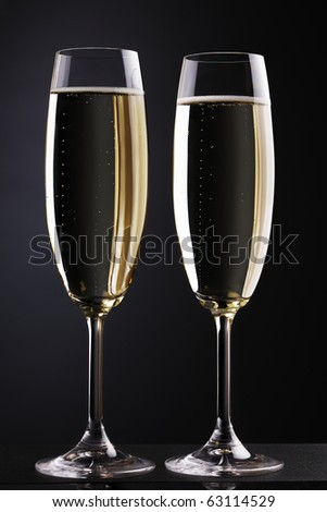 Champagne flutes on dark background