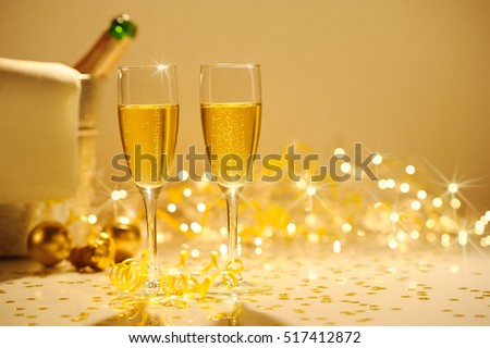 Champagne flutes on table decorated with streamer and gold confetti