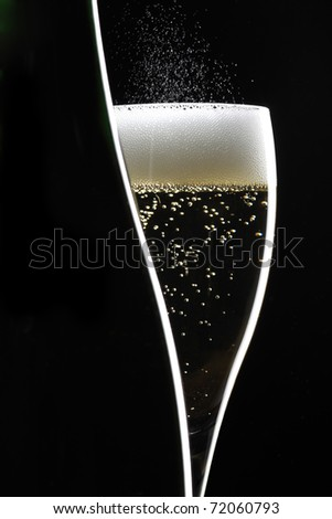 champagne glass and bottle on black background