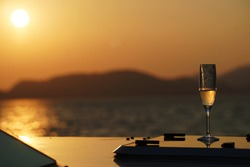 Champagne glass on the yatch that sailling in the sea with sun set.
