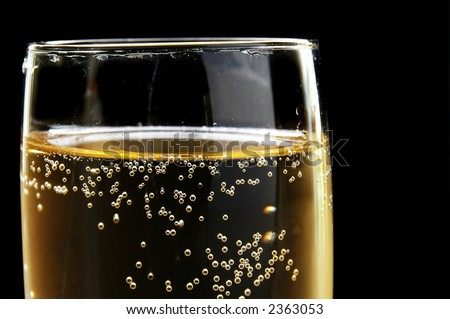Champagne glass with bubbles on dark background. Could also be used as beer.
