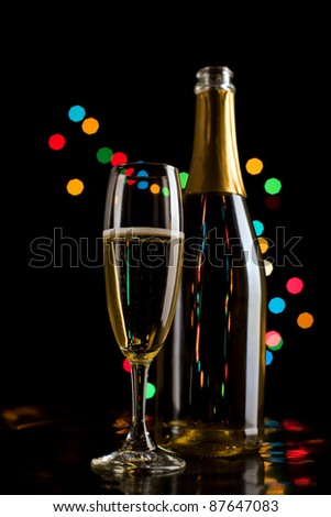 Champagne glasses and bottle on bokeh background. New Year celebration.