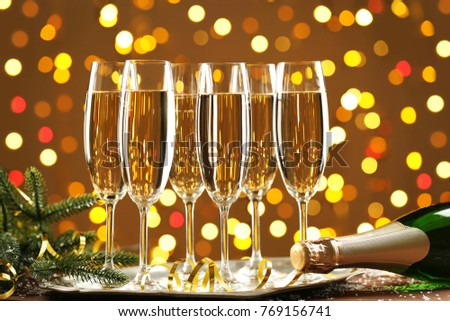 Champagne glasses and bottle on lights background #769156741