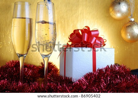 Champagne glasses  and gift box on celebratory table