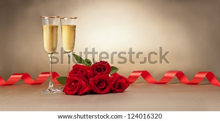Champagne glasses and roses in front of beige background