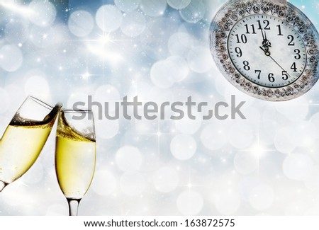 Champagne glasses, clock and fireworks at midnight