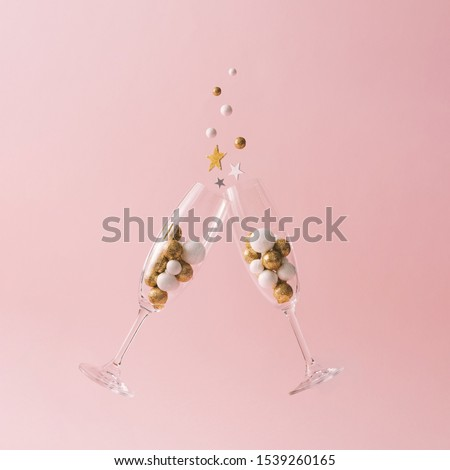 Champagne glasses filled with golden and white glitter decoration and pink background. Celebration minimal Christmas party.