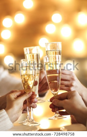 Champagne glasses in hands on golden background. Party and celebration concept #728498758