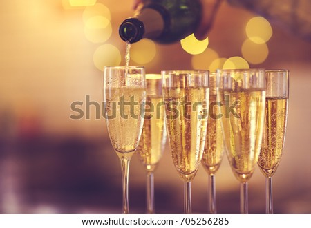 Champagne glasses on gold background. Party and holiday celebration concept #705256285