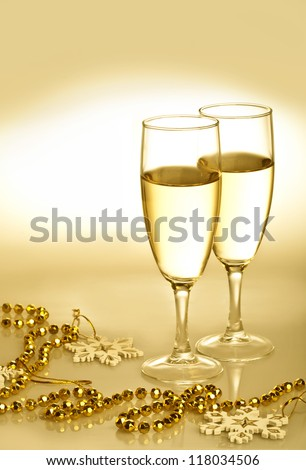 Champagne glasses with gold ornaments and snowflakes