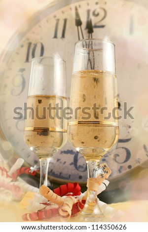 Champagne in glasses with ribbons with new years countdown vintage clock in the background